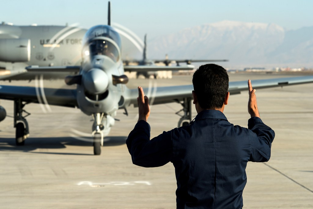 A member of the Afghan air force marshals in an A-29 Super Tucano at Hamid Karzai International Airport near Kabul, Afghanistan, January 15, 2016. Picture taken January 15, 2016.