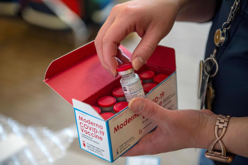 In this file photo taken on December 24, 2020 a person unpacks a special refrigerated box of Moderna Covid-19 at the East Boston Neighborhood Health Center.