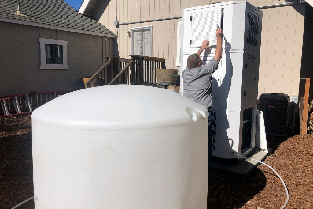 Ted Bowman, design engineer with Tsunami Products, installs a unit in homeowner Don Johnson's backyard in Benicia, Calif., Sept. 28, 2021.