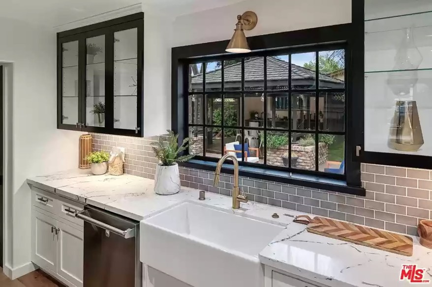 The kitchen has a farmhouse sink and golden features.