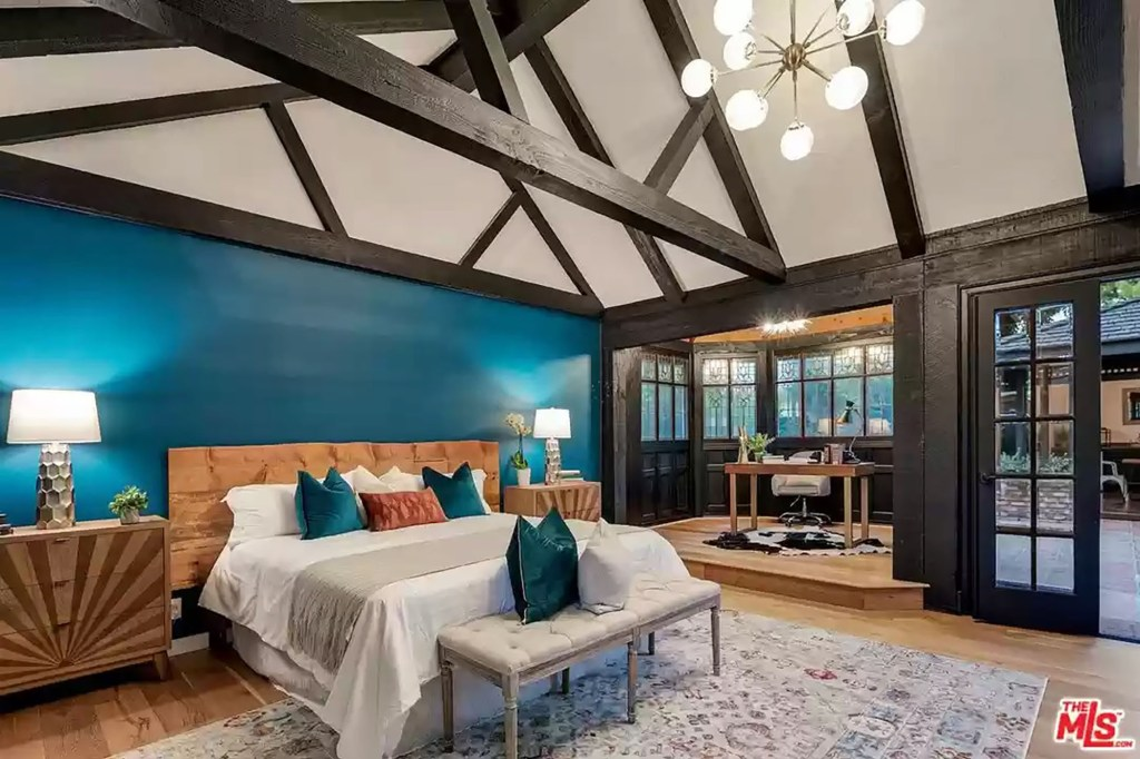 A bedroom with wooden beams is pictured.