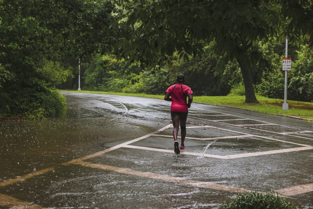 A runner exercising in Prospect park during tropical storm Henri in the Brooklyn