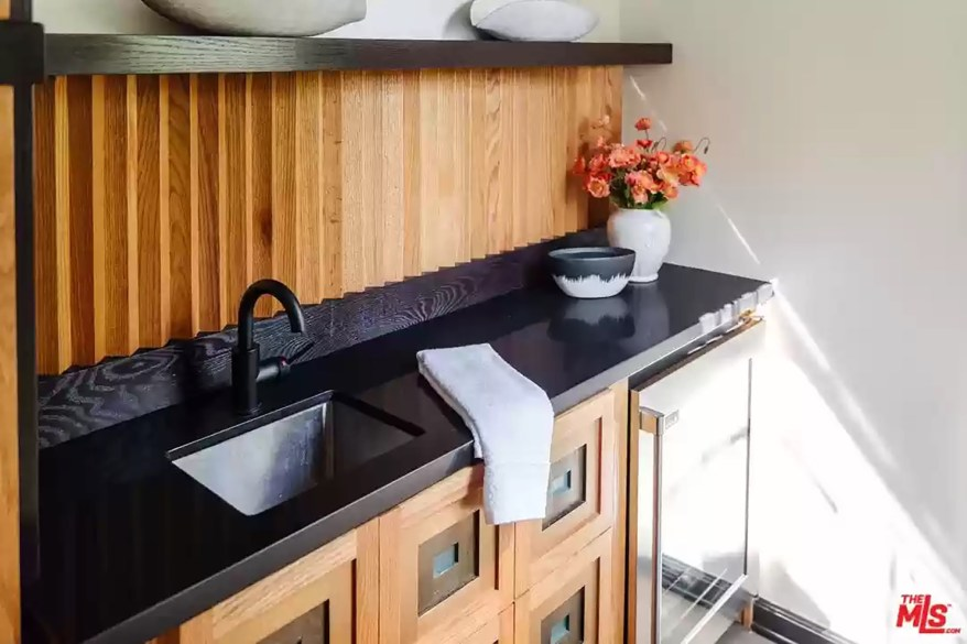 A kitchenette with a sink and wine fridge is pictured.
