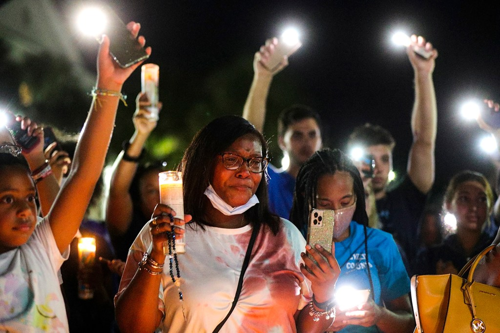 Attendees raise candles and phone flashlights to music during a candlelight vigil for Miya Marcano at Arden Villas.