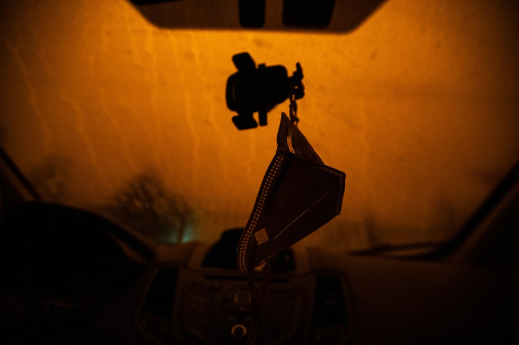 An N95 facemask hangs from the windshield as is silhouetted by the orange sky produced by the wildfires smoke in Northern California seen in Oakland, Calif., on Wednesday, Sept. 9, 2020.