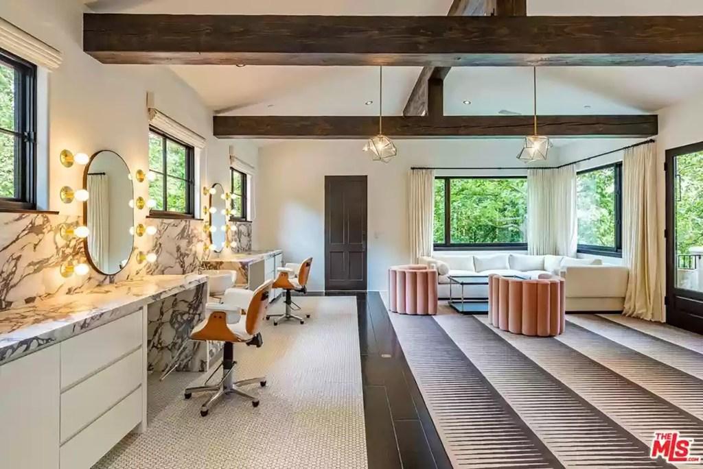 This vanity area is in a room with peaked, beamed ceilings.