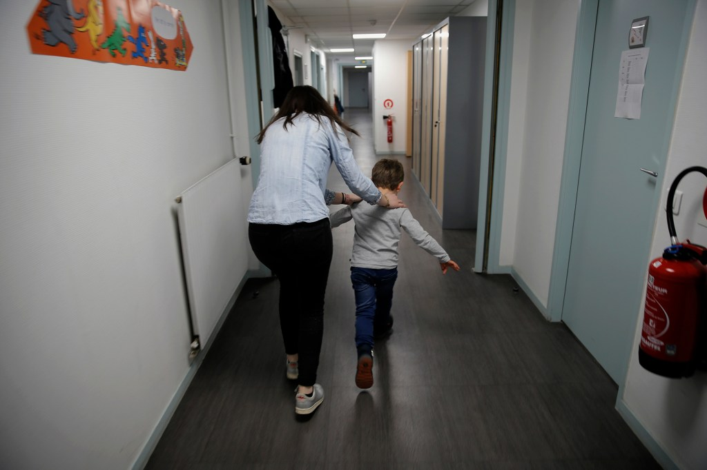 In this Tuesday, March 2, 2021 file photo, Maelle Allanore, a psychomotor therapist runs down a corridor with a boy in the pediatric unit of the Robert Debre hospital, in Paris, France.