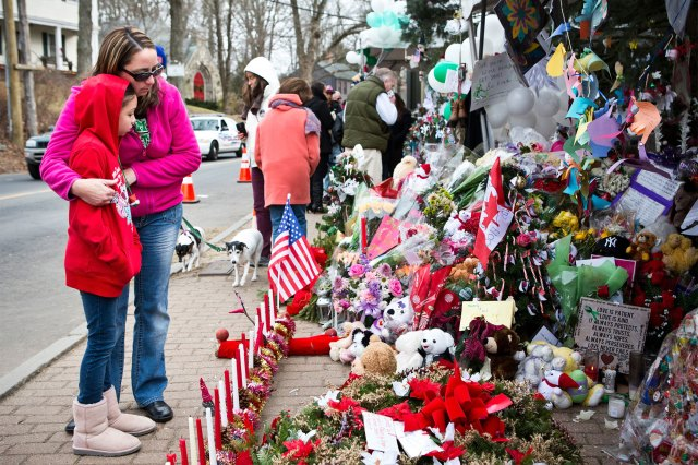 Deborah Gibelli holds her daughter, Alexandra Gibelli, age 9, while looking at a memorial for those killed in the school shooting at Sandy Hook Elementary School, on December 24, 2012.
