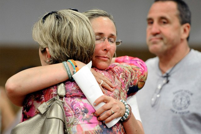 Scarlett Lewis, center, mother of Sandy Hook Elementary School shooting victim Jesse Lewis, hugs Lynn McDonnell, left, mother of victim Grace McDonnell, as Neil Heslin, right, father of Jesse Lewis watches after a public forum in Newtown, Conn., in 2013.