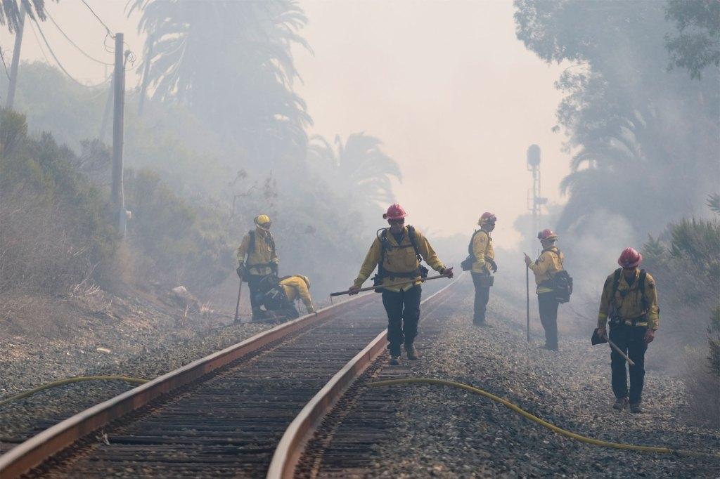 Firefighters work alongside railroad tracks in Goleta, Calif. on Oct. 13, 2021.