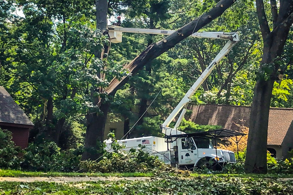 In this Aug. 7, 2020 file photo, workers clean up tree damage in Glastonbury, Conn. in the wake of Tropical Storm Isaias.