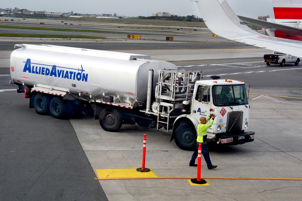 A jet fuel truck on the tarmac preparing to fuel a plane