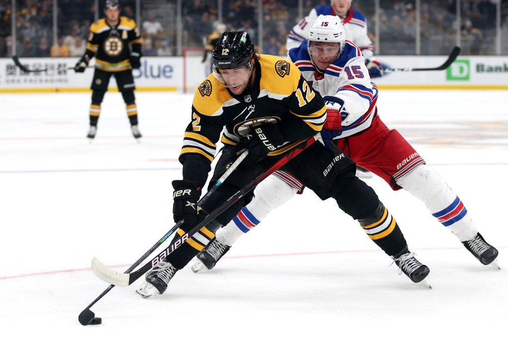 Julien Gauthier battles for a puck against the Bruins in an Oct. 2, 2021 preseason game.