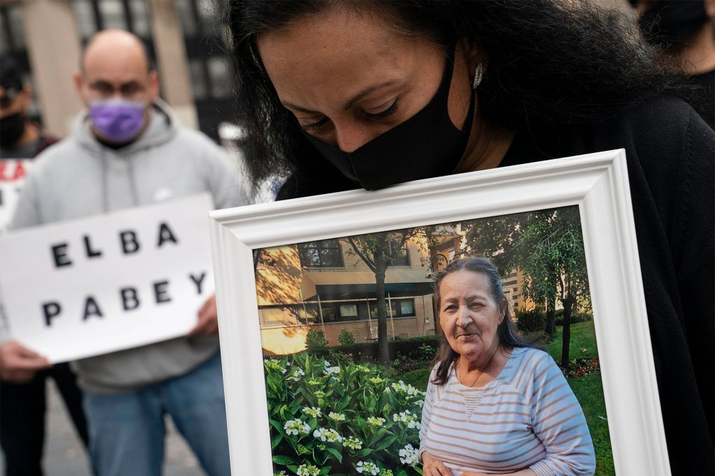 Haydee Pabey holds a picture of the deceased Elba Pabey as demonstrators gather for a rally decrying New York Governor Andrew Cuomo's handling of nursing homes during the previous years outbreak of COVID-19
