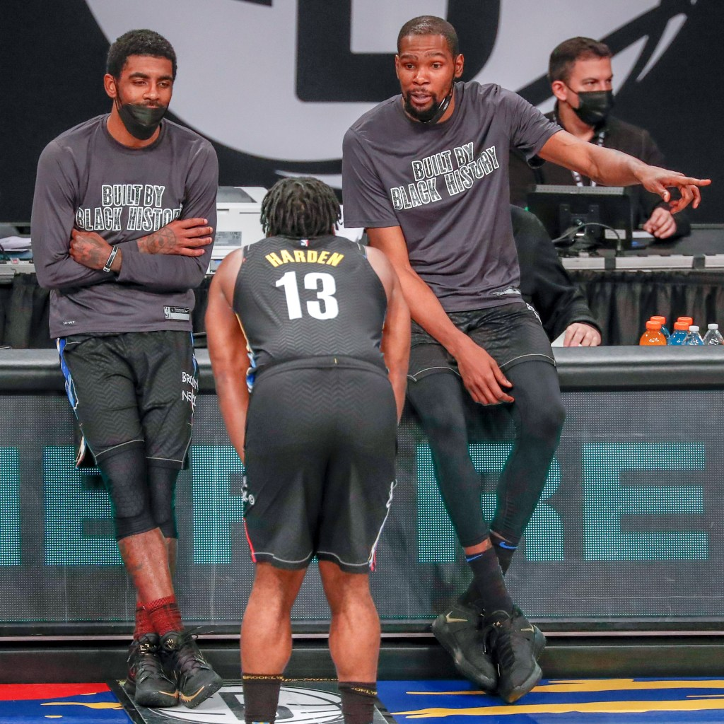 Kyrie Irving (left) and Kevin Durant (right) talk with James Harden.