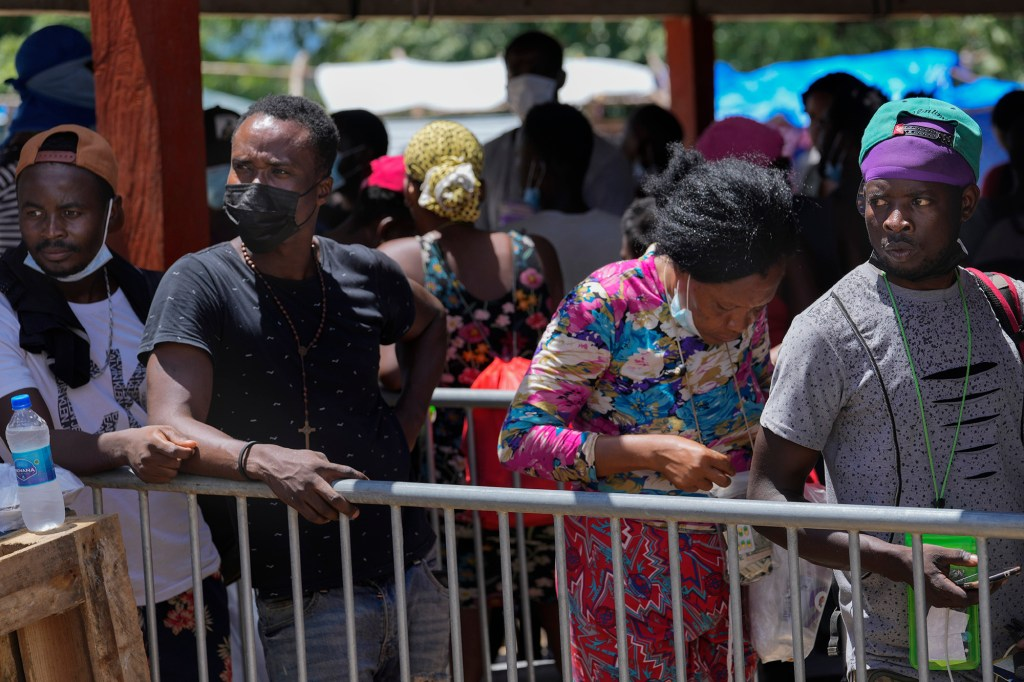 Migrants, many from from Haiti, stand in line to board a bus that will transport them to another shelter on their journey through Panama, trying to reach the United States, in Lajas Blancas, Darien province, Panama, Friday, Oct. 1, 2021.