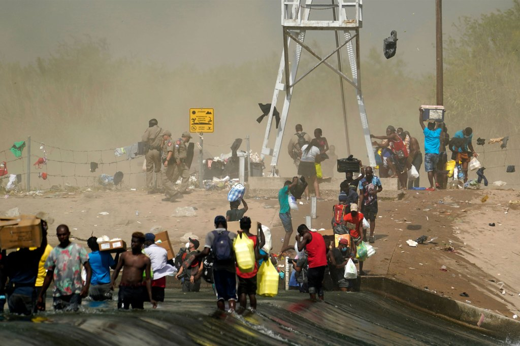 A dust storm moves across the area as Haitian migrants use a dam to cross into the United States.