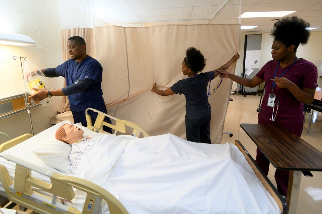 Student nurses Chukwuka Asakwe, Nazarine Beweh and Nicole Obisie attend to a Patient CareManikin in a training simulation at an education lab of the License Practical Nursing program at Delaware County Technical School in Broomall, PA, on January 28, 2020.