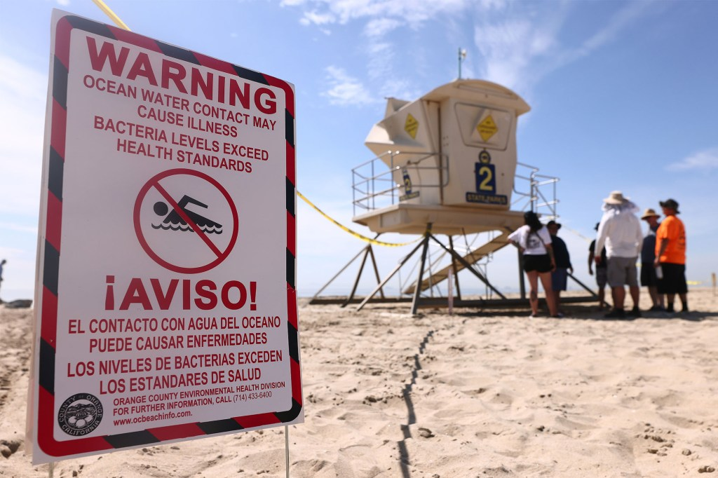 A sign warning people not to swim in the water at Huntington Beach amid the oil spill.