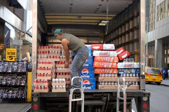 A worker unloads a truckload of bottled soda