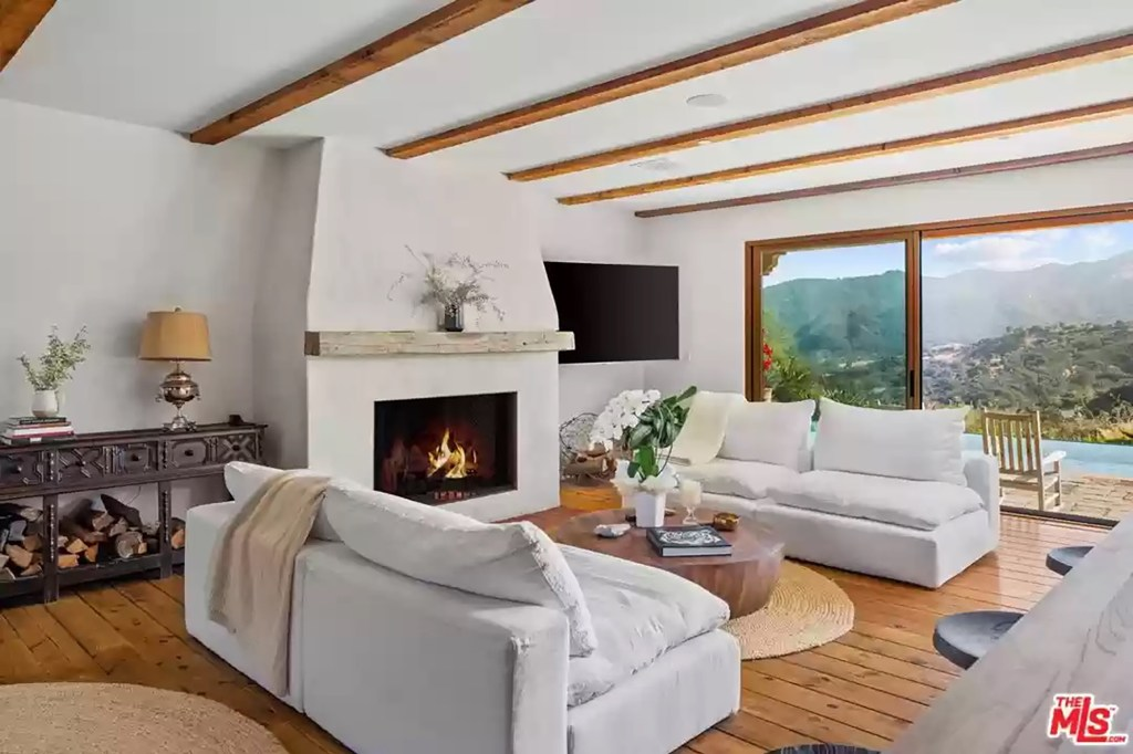 A wood-burning fireplace is in this wood-beamed ceiling.