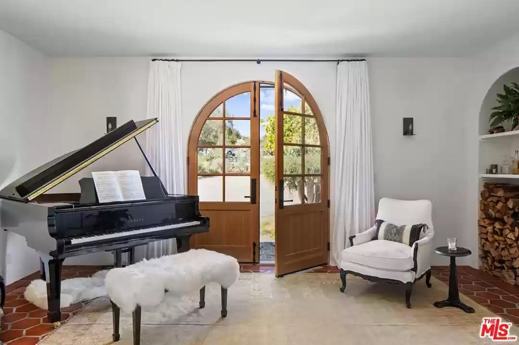 An arched wood door leads outside.