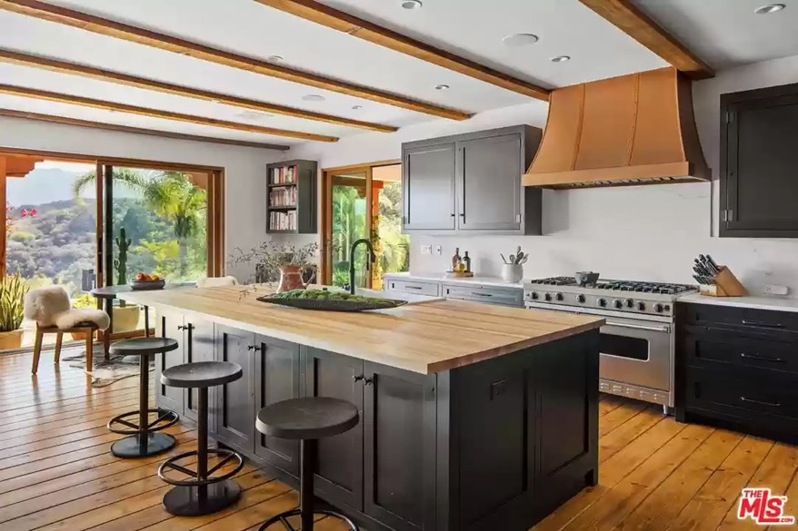 The kitchen has an eat-in bar with a wood countertop.