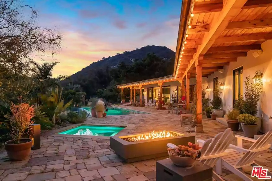 The almost 10-acre lot has a lengthy driveway, oak trees, meadows, lawns, hiking trails and stone and tile patios, according to the listing.