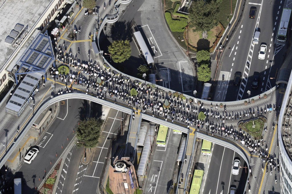 Photo taken Oct. 8, 2021, from a Kyodo News helicopter shows commuters forming a long line in front of JR Kawaguchi Station in Kawaguchi in Saitama Prefecture, eastern Japan, on the morning after a magnitude-5.9 earthquake jolted the Tokyo region and disrupted train services.