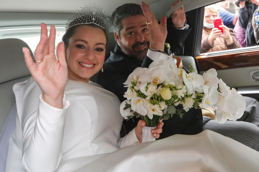 Grand Duke of Russia George Mikhailovich Romanov and his bride Victoria Romanovna Bettarini wave as they leave by car from their wedding ceremony.