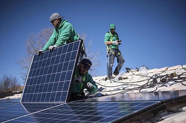 Workers installing rooftop solar panels from SolarCity