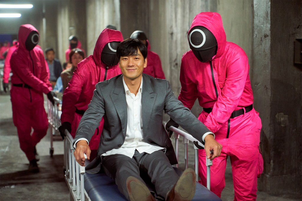 """A smiling man sits on a gurney while a person in a pink jumpsuit and mask tends to him in """"Squid Game."""""""