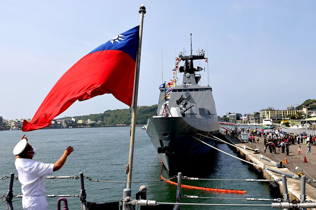 A navy soldier adjusts a Taiwan flag onboard ROCS Chang Chien (PFG2-1109) ahead of the National day celebration in Kaohsiung, Taiwan, October 9, 2021.