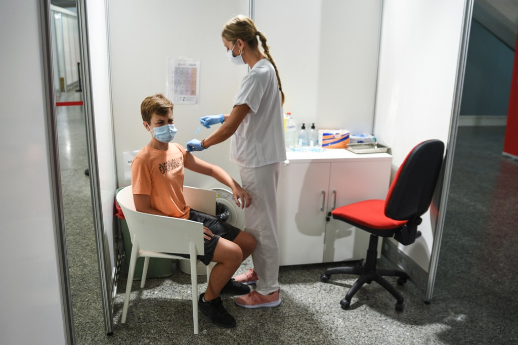 A health worker vaccinates a teenager with the first dose of the Moderna vaccine in the City of Arts, on 16 August, 2021 in Valencia, Valencian Community, Spain.
