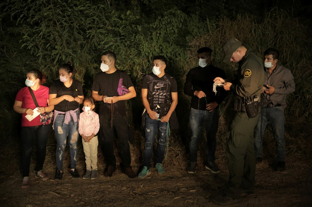 Several migrants detained by US border patrol after crossing into the US illegally.