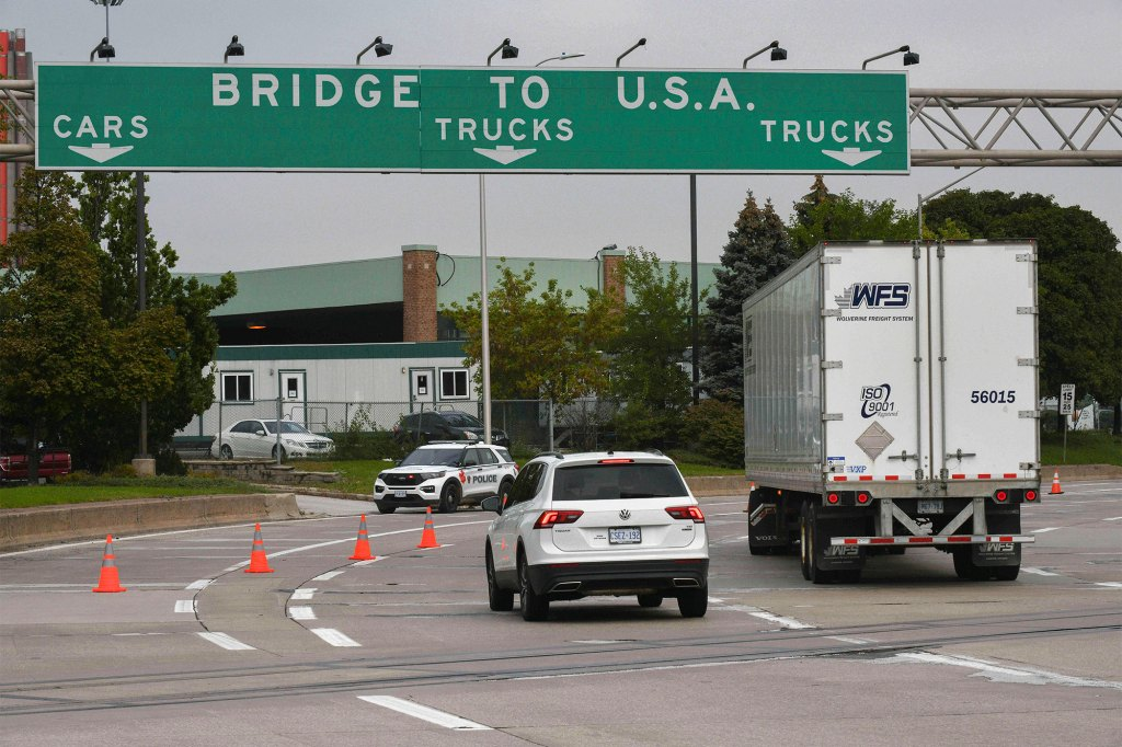 Traffic moves towards a police car by the Ambassador Bridge border crossing in Windsor, Ontario, Monday, Oct.4, 2021.
