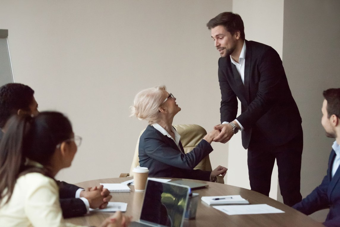 businessman and businesswoman shaking hands during meeting