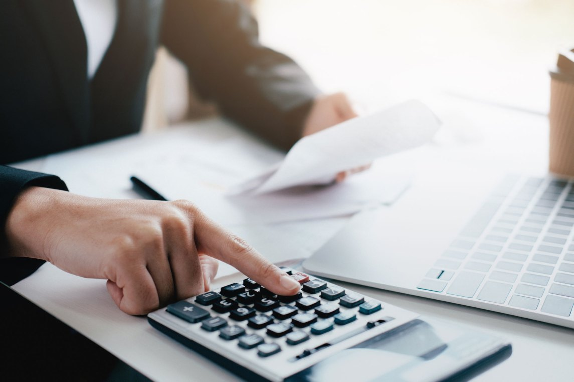 man calculating business expenses with a calculator