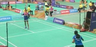 Tunggal junior Indonesia, Putri Kusuma Wardani (kiri), memastikan kemenangan Indonesia 3-0 atas Singapura, usai menaklukan Insyirah Khan, 21-14 dan 21-16, pada Minggu (15/7). (Adt/NYSN)