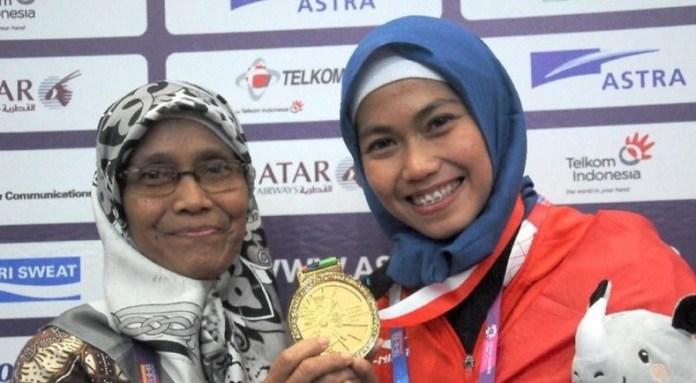 Defia Rosmiar bersama sang ibu, Kaswati, usai meraih medali emas pertama bagi kontingen Indonesia, dari cabor Taekwondo, nomor Women Individual Poomsae, Jakarta Convention Center (JCC) Senayan, Jakarta, pada Minggu (19/8). (istimewa)