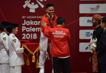 Lifter Indonesia Eko Yuli Irawan mendapatkan pengalungan medali emas oleh Presiden Joko Widodo, usai menjadi yang terbaik dalam cabor angkat besi kelas 62 kilogram putra Asian Games 2018, di JIExpo, Selasa (21/8). (Riz/NYSN)