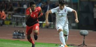 Bek kanan Timnas U-23, I Putu Gde Juni Antara (2), membayangi pemain Hongkong Wai Keung Chung (9), pada laga penentuan Juara Grup A, di Stadion Patriot Candrabaga, Bekasi, Senin (20/8) malam. Indonesia berhasil unggul 3-1 dan lolos ke babak 16 besar cabor sepak bola putra. (Pras/NYSN)