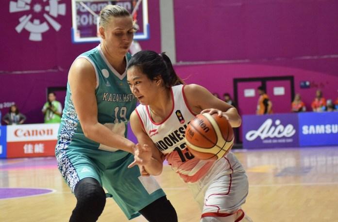 Dengan tinggi 167 cm, Shooting Guard Timnas basket putri Indonesia, Christine Aldora Tjundawan (13), berduel melawan forward Kazakhstan, Oxana Ossipenko (19) yang berpostur 186 cm, pada babak penyisihan Grup X bola basket putri, Asian Games 2018, Minggu (19/8). (Riz/NYSN)