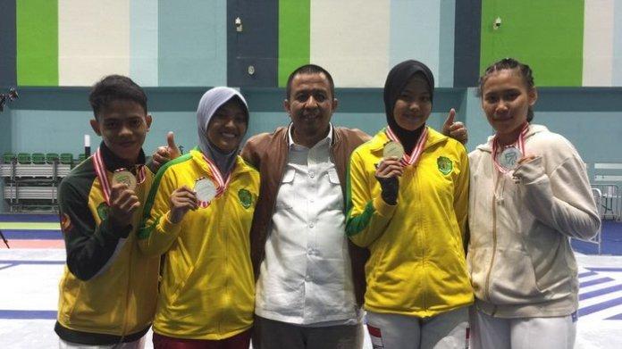 Ketua Pengprov IKASI Kaltim, Muslimin bersama para atlet peraih medali Kejuaraan Nasional (Kejurnas) Anggar 2018 di GBK Arena, Senayan, pada Sabtu (3/11). Eks atlet Asian Games 2018 yang baru berusia 16 tahun, Gabhy Novitha (hijab hitam), berhasil menyabet medali emas, untuk kategori Sabel putri junior. (tribunnews.com)