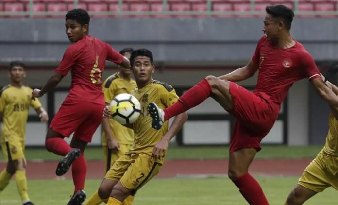 Bek Timnas U-22 sekaligus kapten, Andy Setyo (2/merah), tengah berduel dengan tim Bhayangkara FC, pada laga uji coba jelang Piala AFF U-22, di Stadion Patriot Candrabhaga, Bekasi, Rabu (6/2). Kedua tim akhirnya bermain imbang 2-2. (Bola.com)