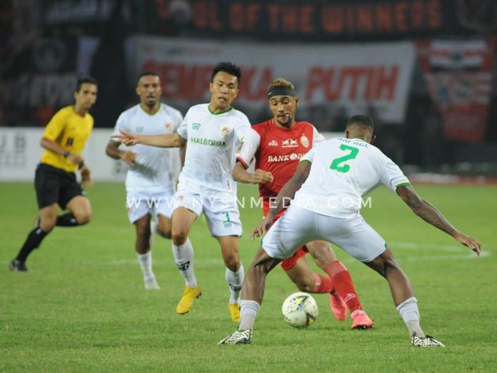 Bruno Martos, pemain Persija berhadapan dengan dua pemain Kalteng Putra, Rafael Bonfim dan Wasyiat Hasbullah