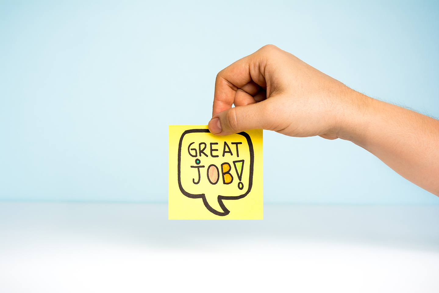 hand holding post-it note with great job written on it