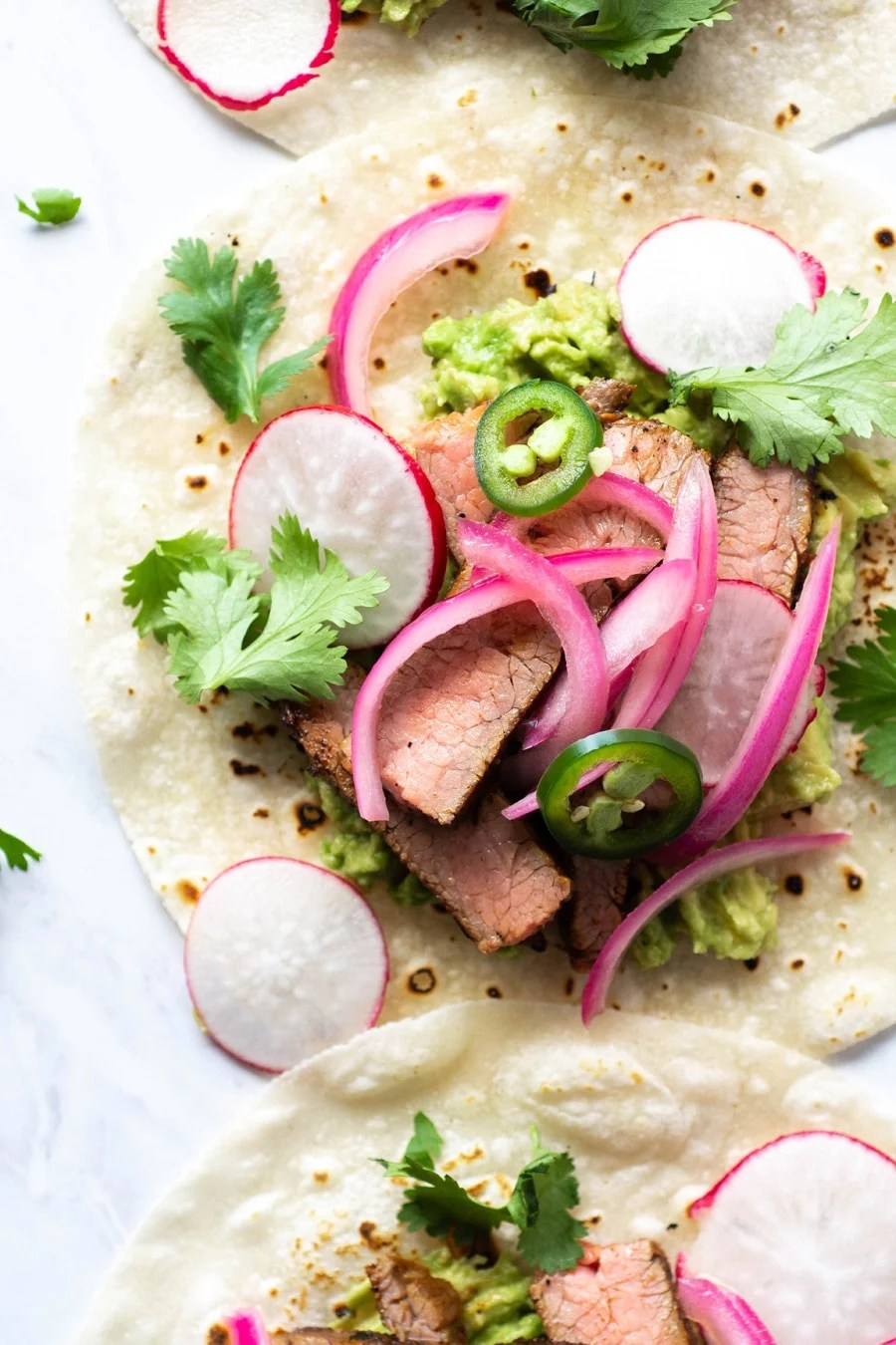 Close up shot of a steak taco on a white background with cilantro, thinly sliced jalapeno, pickled red onions