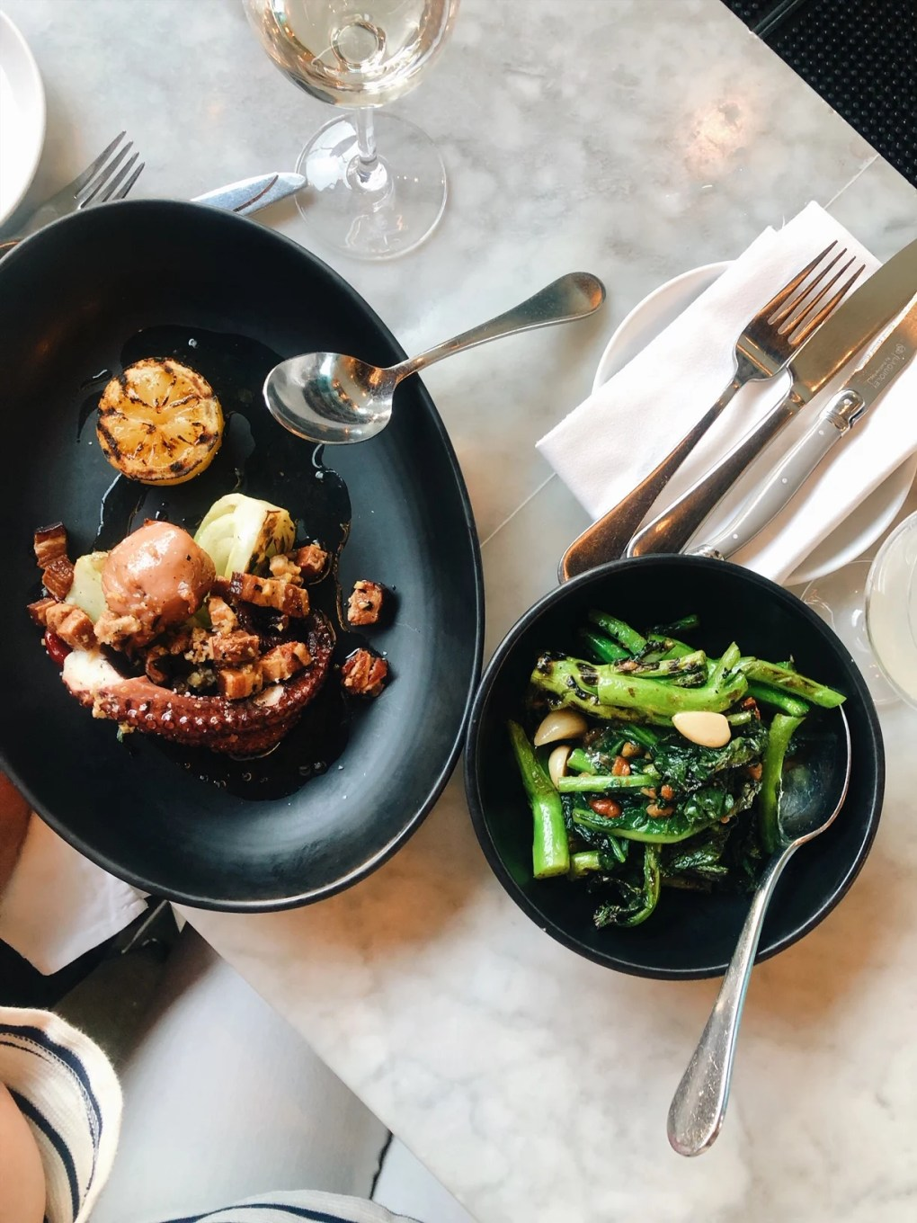 Overhead view of grilled octopus and chinese broccoli on the marble bar top at Joule Restaurant in Seattle.