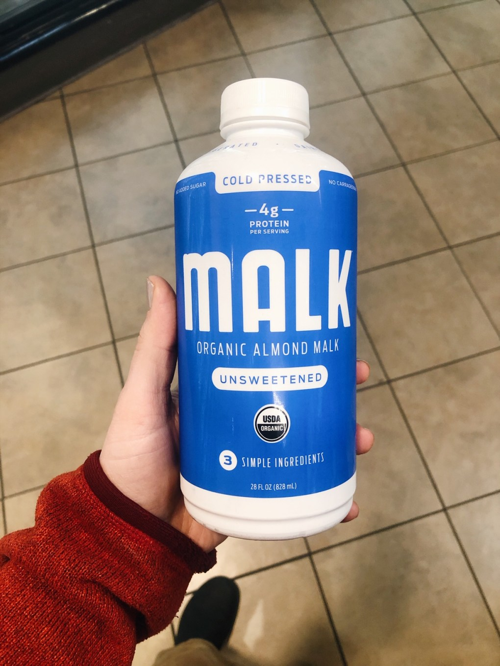 Holding a bottle of malk organics almond milk in the grocery store